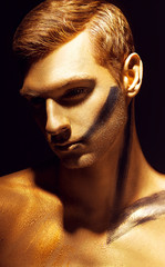 Dramatic art portrait of man in bronze paint on his body and gol