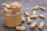 Jar of peanut butter with nuts. On wooden texture.