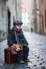 Cute boy, sitting on a suitcase, holding a teddy bear