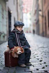 Cute boy, sitting on a suitcase, holding a teddy bear
