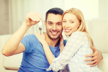 smiling couple holding keys at home