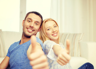 smiling happy couple at home showing thumbs up