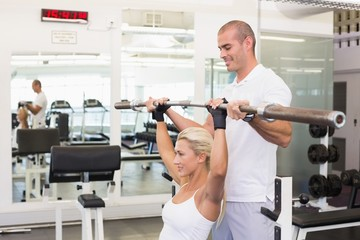 Trainer helping woman with lifting barbell in gym