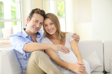 Middle-aged couple at home relaxing in couch