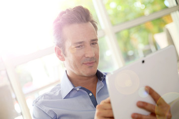 Portrait of middle-aged man at home using tablet