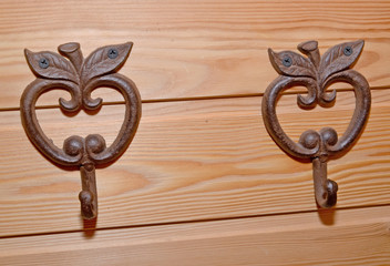 Two metal hooks hangers in the form of apples on a wooden wall