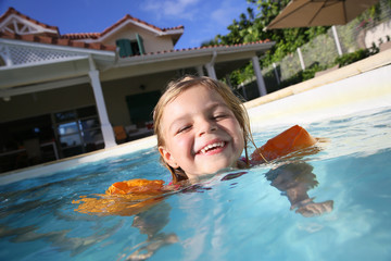 Cheerful 4-year-old girl playing in pool