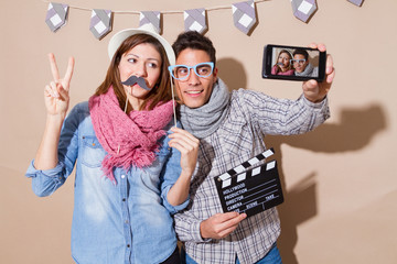 Young couple taking selfie in a Photo Booth party