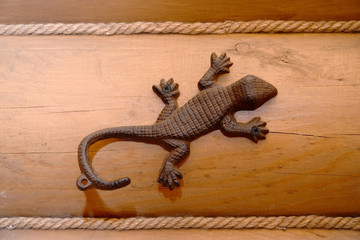 Metal hanger with a hook in the form of a lizard on a timbered w