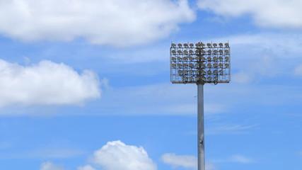 Stadium spot lights, beautiful blue sky and clouds running.