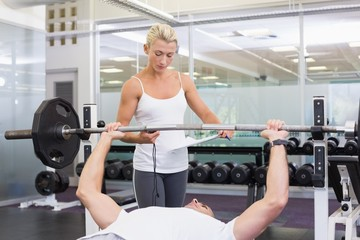 Trainer helping man with lifting barbell in gym