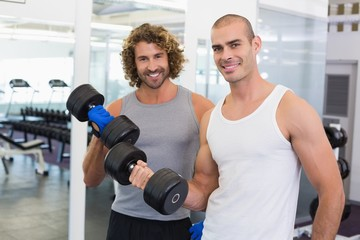 Sporty men exercising with dumbbells in gym