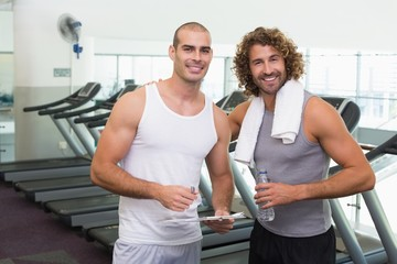 Smiling male trainer and fit man at gym