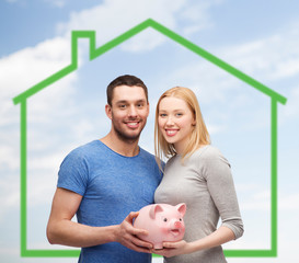 smiling couple holding piggy bank over green house