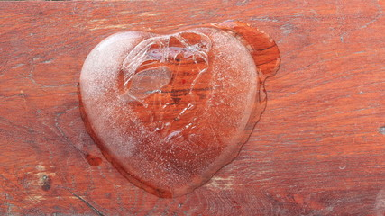 Ice heart shape melt on wood background.time lapse clip.