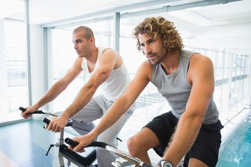 Men working on exercise bikes at gym