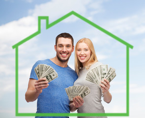 smiling couple holding money over green house