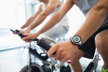 Mid section of men working on exercise bikes at gym