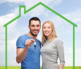 smiling couple holding key over green house