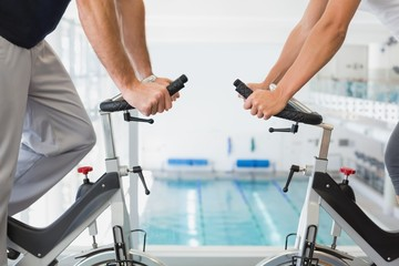 Mid section of couple working on exercise bikes at gym