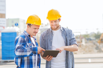 smiling builders in hardhats with tablet pc