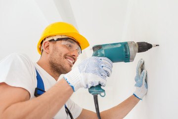 smiling builder in hardhat drilling wall indoors