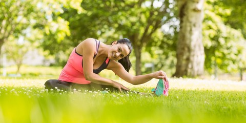 Smiling fit brunette stretching on the grass