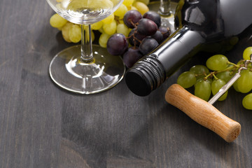 bottle of red wine and grapes on a wooden background, close-up