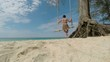 Woman resting on the beach on a swing.