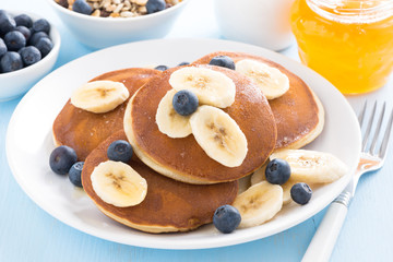 pancakes with banana, honey and blueberry on a plate