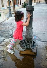 Niña jugando en la fuente