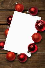 Composite image of red christmas baubles surrounding white page