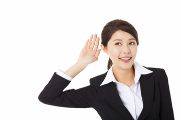 Young business woman putting hand to ear and listening