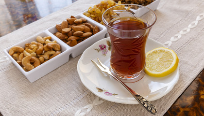 Azerbaijani tea with lemon and set nuts and sweets