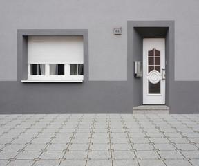 Renovierte Altbaufassade in grau mit PVC Haustür und Fenster