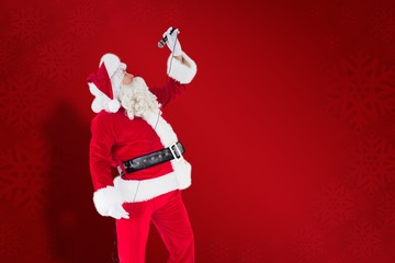 Composite image of happy santa claus singing with microphone