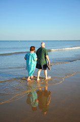 Pareja de ancianos caminando por la playa, España