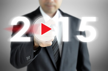 Businessman pointing  to 2015 on virtual screen