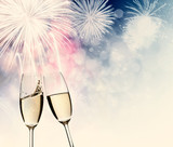 New Year's - toasting with champagne glasses against fireworks a