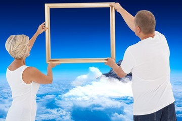 Composite image of mature couple hanging up picture frame