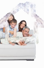 Composite image of children lying on their parents on sofa