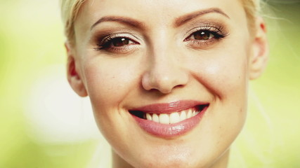 Attractive blonde young woman smiles into the camera. Close up