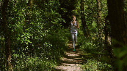 Woman running in summer forest