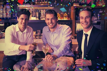 Composite image of handsome friends having a drink together
