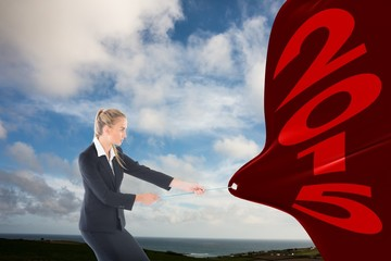 Composite image of focused blonde businesswoman pulling a rope