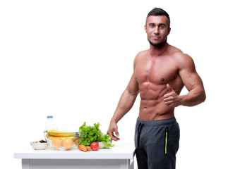 Happy muscular man standing with thumbs up near healthy food