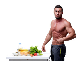 Handsome muscular man pointing at healthy food