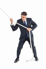 Businessman in suit pulling a rope
