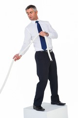 Businessman standing on a cube and pulling rope