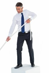 Businessman standing on cube pulling rope